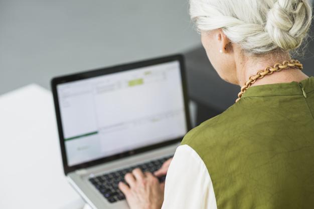 rear-view-senior-woman-using-laptop_23-2147918214
